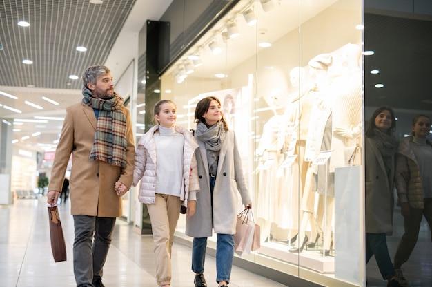 Счастливые родители и дочь смотрят на новую коллекцию повседневной одежды в витрине магазина, отдыхая в торговом центре во время сезонной распродажи