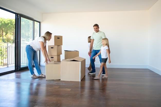 Счастливые родители и дочери открывают коробки и распаковывают вещи в своей новой пустой квартире