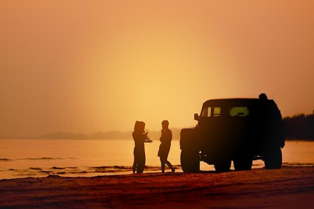 Счастливые родители и ребенок веселятся, играя в песок на летних каникулах на пляже
