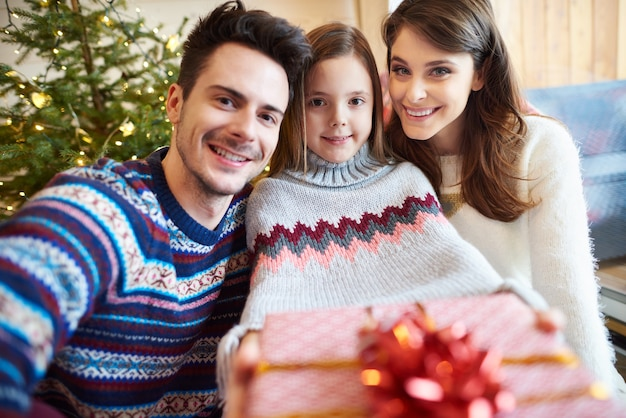Счастливые родители и ребенок с подарочной коробкой