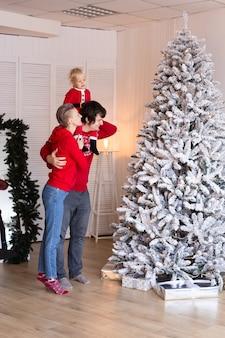 幸せな両親と幼い息子が家でクリスマスツリーを飾っています。メリークリスマス、そしてハッピーニューイヤー