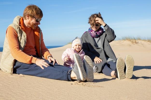 Счастливые родители и милый маленький ребенок в теплой одежде, проводят свободное время на море, вместе сидят на песке