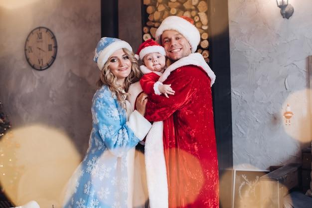 幸せな両親と抱擁に立っているwamrコートを着た彼らのかわいい子供。休日のコンセプト