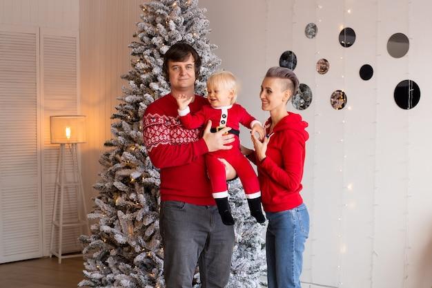 幸せな両親と家でクリスマスを待っている彼らのかわいい息子の男の子。家で家族のクリスマス。