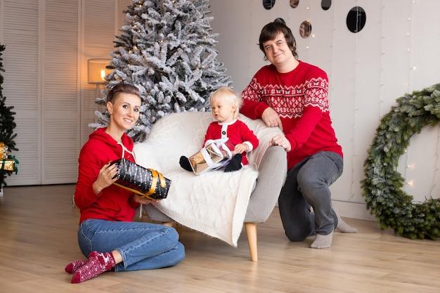 幸せな両親とその幼い息子が贈り物を交換します。メリークリスマスとハッピーホリデー