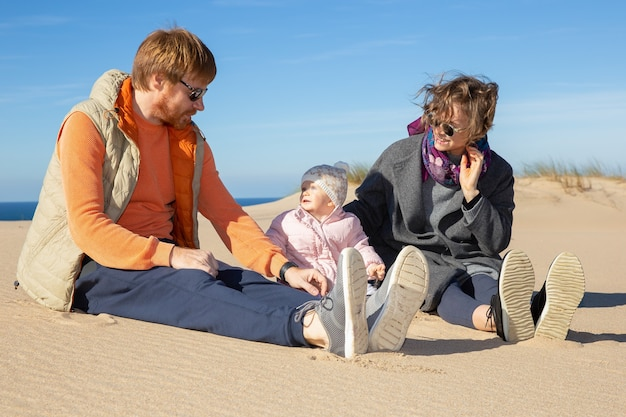 Happy parents and cute baby girl wearing warm clothes, enjoying leisure time at sea, sitting on sand together