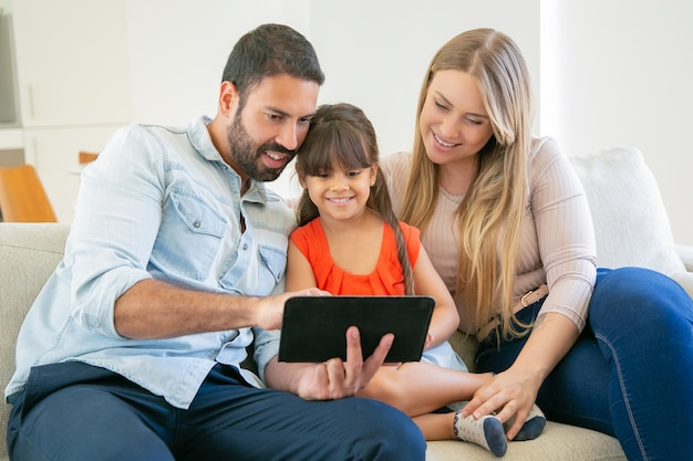 Happy parents and cute daughter sitting on couch, using tablet for video call or movie watching.