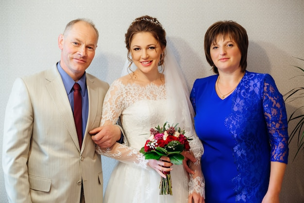 Happy parents and the daughter who gets married, dressed in a wedding dress and a bouquet in her hand