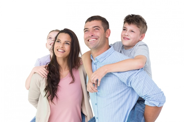 Happy parents giving piggyback ride to children while looking up