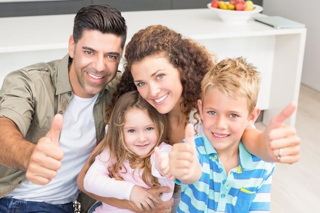 幸せな親たちは幼い子供たちと親指をあげている