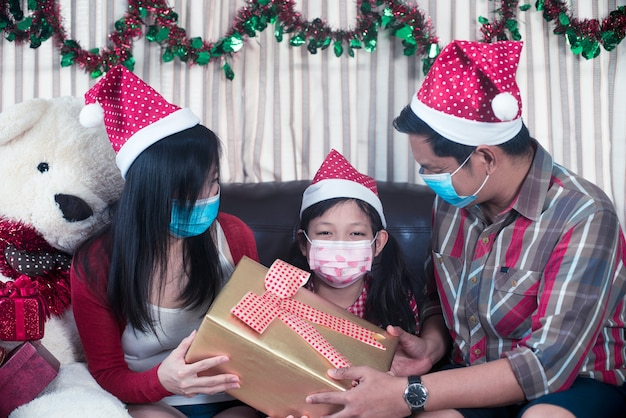 Happy parents giving xmas present for daughter with wear face mask.family in christmas interior