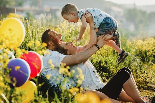 Счастливые родители развлекаются с ребенком на зеленой лужайке под елкой
