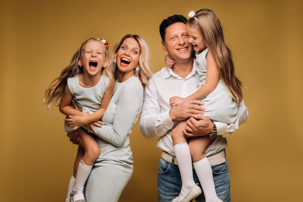행복한 부모는 자녀를 팔에 안고 노란색 배경에 미소를 짓습니다. 감정적 인 4 인 가족.