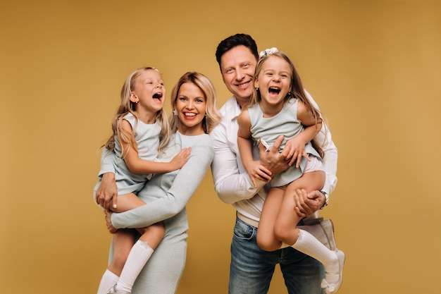 Happy parents hold their children in their arms and smile on a yellow background. an emotional family of four