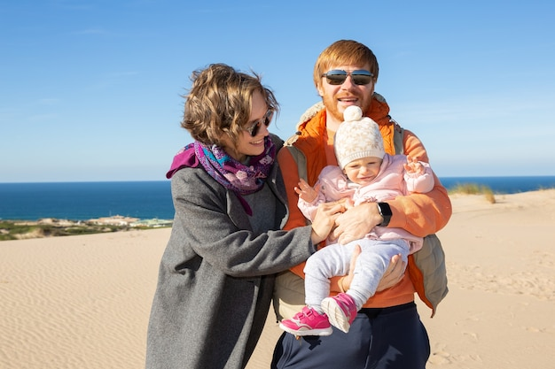 바다에서 모래에 서있는 동안 팔에 귀여운 아기 딸을 들고 행복 한 부모