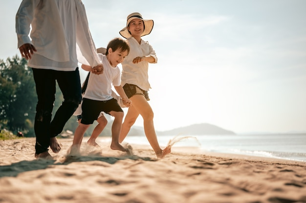 Happy parents and kid having fun with playing sand in summer vacation on the beachtravel