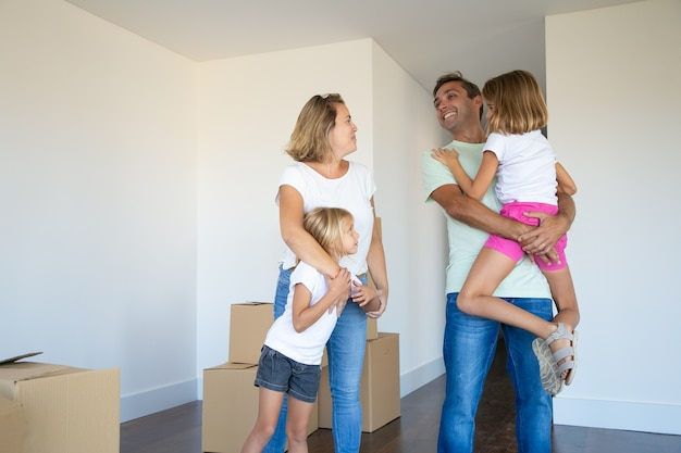 Happy parents and kids enjoying moving into new flat, standing near stack of boxes and hugging