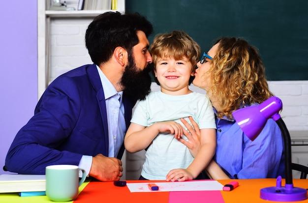 幸せな両親は幼い息子にキスします。一緒に学校教育。子供の教育。子育て。