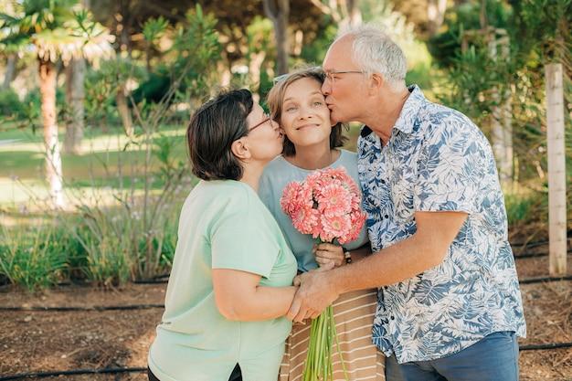 Genitori felici che baciano la loro figlia adulta