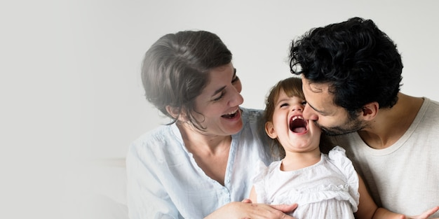 Happy parents laughing together with daughter
