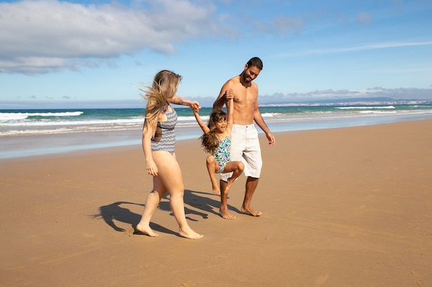 Happy parents and little girl wearing swimsuits, walking on golden sand from sea