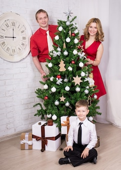 Happy parents and little son decorating christmas tree at home