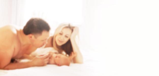 갓 태어난 딸을 바라보는 행복한 부모. 광고 텍스트에 대한 흐릿한 이미지입니다.