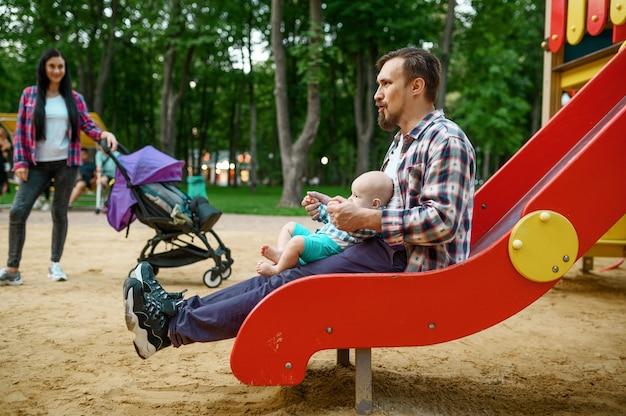 행복 한 부모 여름 공원에서 놀이터에서 작은 아기와 함께 재생