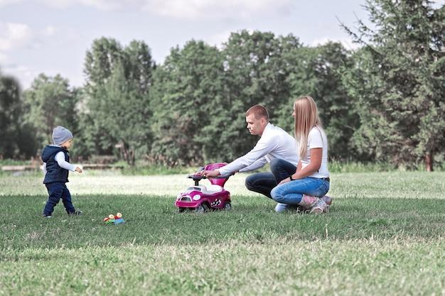 Счастливые родители играют со своим маленьким сыном на лужайке в парке