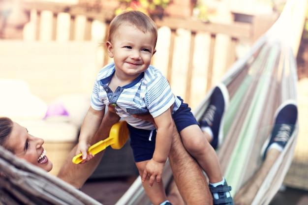 ハンモックで男の子と遊ぶ幸せな親