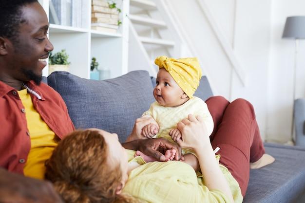 Счастливые родители играют со своей девочкой, отдыхая на диване в гостиной