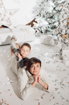 Happy parents showing christmas decoration on tree for little son.