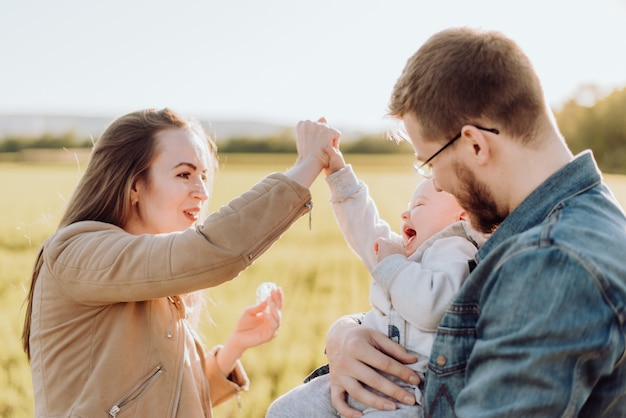 Happy parents spend time and play with their baby in the summer on a sunny day at sunset