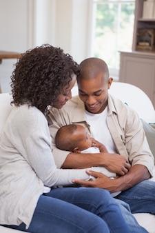 幸せな親、ソファに赤ちゃんと時間を過ごす