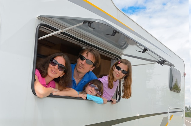 Happy parents traveling with kids and having fun in motorhome