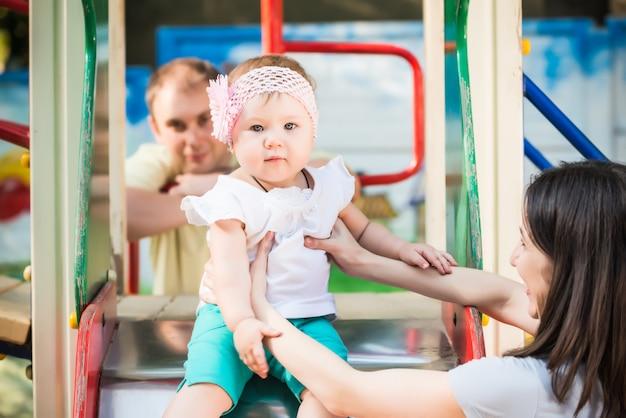Счастливые родители гуляют и играют со своей маленькой дочерью