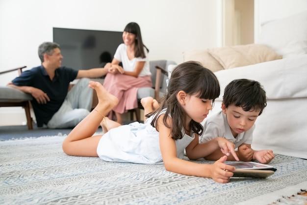 Счастливые родители наблюдают за милыми детьми, лежащими на полу в гостиной, и используют цифровые гаджеты с обучающими приложениями.