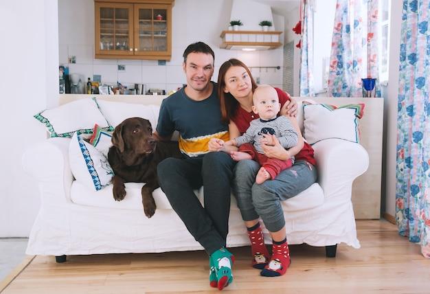Счастливые родители с ребенком и собакой на диване в домашнем интерьере концепция семьи образа жизни