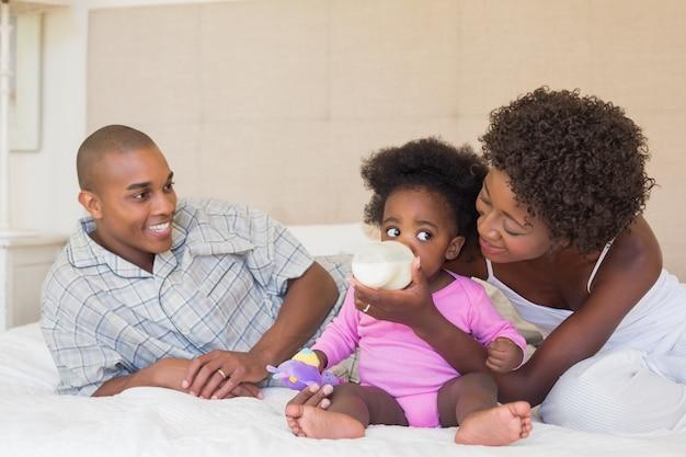 幸せな両親、赤ん坊の女の子とベッドで