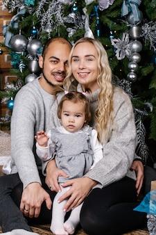 Счастливые родители с ребенком в украшенной комнате на рождество.