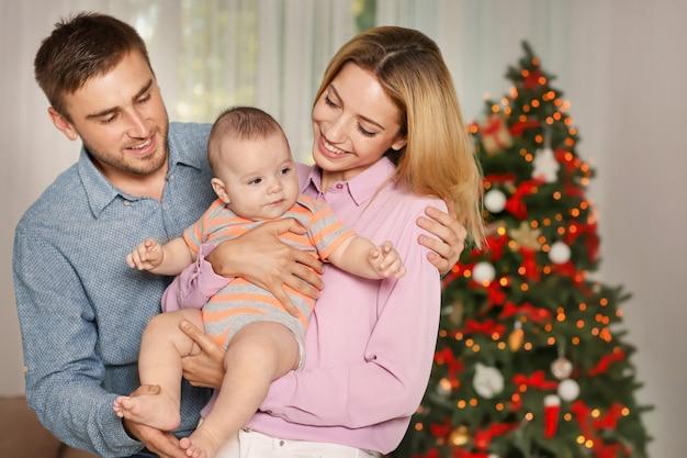 クリスマスの装飾された部屋で赤ちゃんと幸せな親