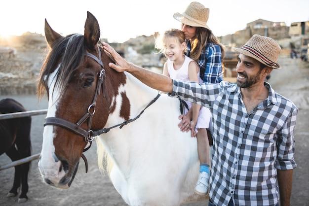 農場の牧場で馬に乗っている娘と幸せな親