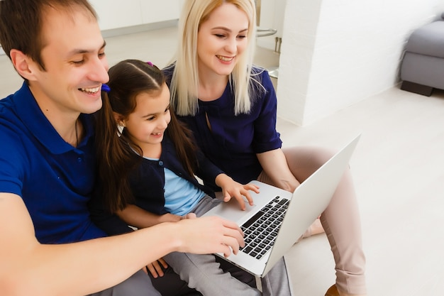 Happy parents with daughter using laptop at home