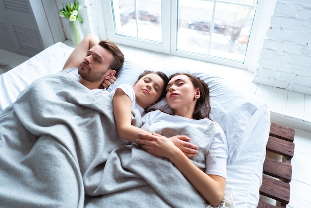 The happy parents with a girl sleeping on the bed