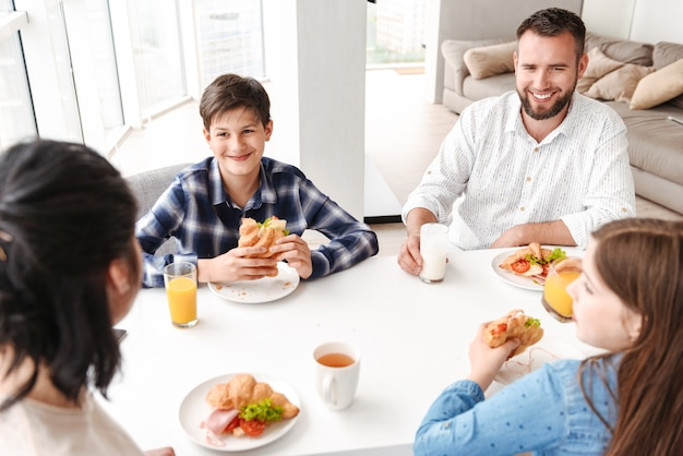 Happy parents with kids 8-10, sitting at table in bright kitchen, and having breakfast while eating croissant sandwiches