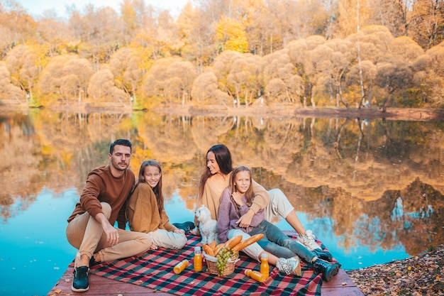 Happy parents with kids at autumn on picnic on the lake