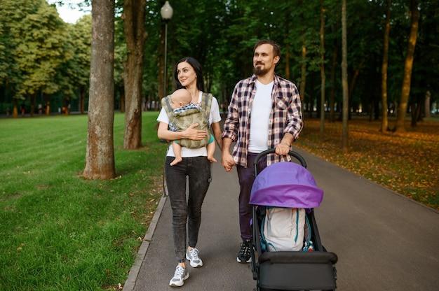 여름 공원에서 보도로 걷는 작은 아기와 함께 행복한 부모