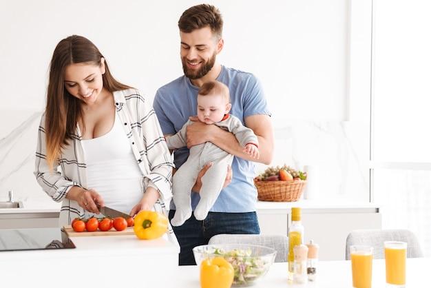 台所で料理をして彼らの赤ん坊の息子を持つ幸せな親。
