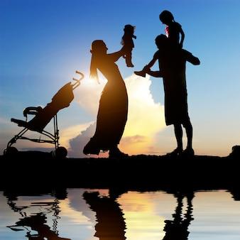 海岸で彼らの小さな子供たちと幸せな親