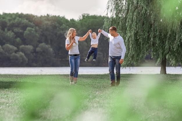 Счастливые родители с маленьким сыном вместе гуляют в весеннем парке. концепция семейного счастья